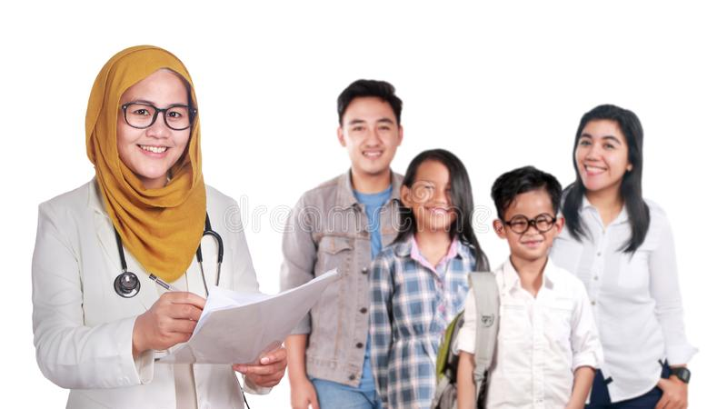 Porträt glücklichen lächelnden weiblichen asiatischen moslemischen Doktors des Vertrauens mit junger Familie, Gesundheitswesen un lizenzfreie stockfotos