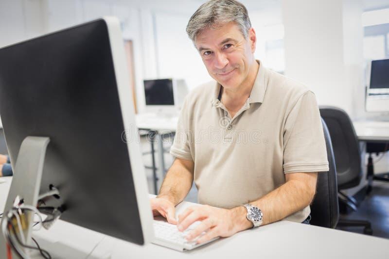 Porträt glücklichen Professors arbeitend an Computer lizenzfreie stockfotos