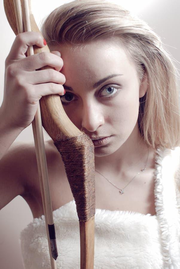 Porträt Holdingbogens u. -pfeiles der jungen Frau des Amazonas-Kriegersmädchens des schönen blonden nah an u. Kamera auf heller W lizenzfreie stockbilder