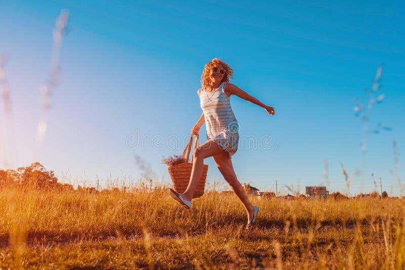 Porträt im Freien der jungen Frau mit dem roten gelockten Haar, das mit einer Tasche von Blumen springt Glückliche Sommerferien lizenzfreie stockfotos