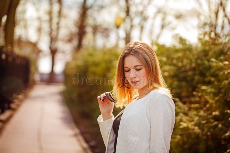 Porträt im Freien der jungen Schönheit aufwerfend auf Straße mit Sonnenbrille am sonnigen Tag Weibliche Mode Junge Frau der Schön lizenzfreie stockfotografie