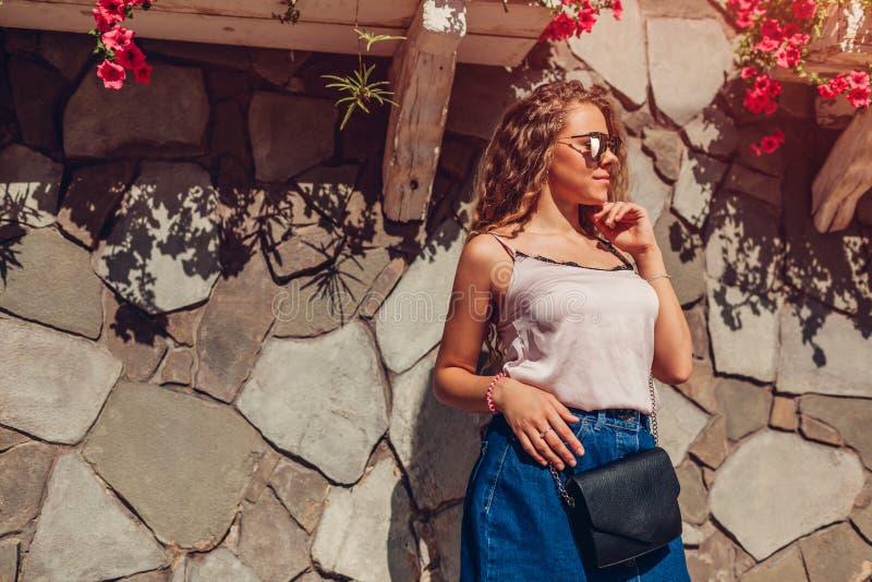 Porträt im Freien der jungen Schönheit mit langer tragender zufälliger Ausstattung des Sommers des gelockten Haares in der Stadt  stockfoto