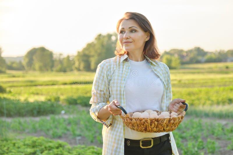 Porträt im Freien der Landwirtfrau mit Korb von frischen Hühnereien, Bauernhof lizenzfreie stockfotos