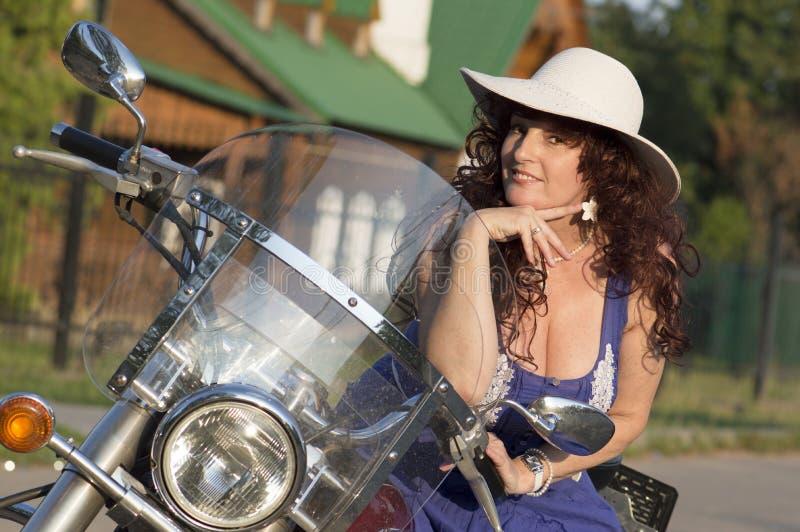 Porträt im Freien der Mittelalterfrau auf dem Motorrad lizenzfreies stockbild