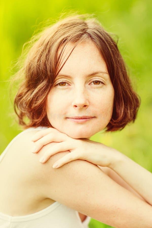 Porträt im Freien der recht sommersprossigen jungen Frau das, die sich umarmt stockbilder