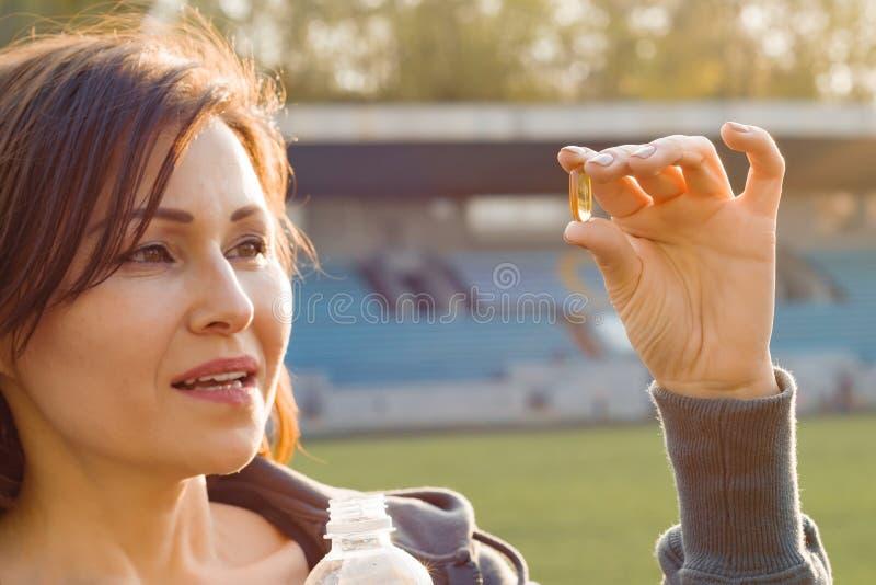 Porträt im Freien der reifen Frau Kapselpille des Vitamins E des Lebertrans, am Stadion nehmend Sport, gesunder Lebensstil und lizenzfreie stockfotografie