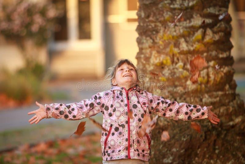 Porträt im Freien des jungen glücklichen Kindermädchens, das mit Herbst L spielt lizenzfreie stockfotos