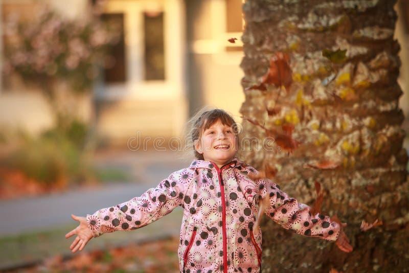 Porträt im Freien des jungen glücklichen Kindermädchens, das mit Herbst L spielt stockbild