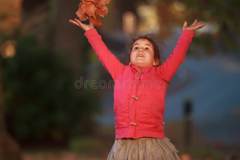 Porträt im Freien des jungen glücklichen Kindermädchens, das mit Herbst L spielt stockfoto