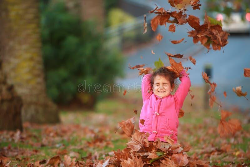 Porträt im Freien des jungen glücklichen Kindermädchens, das mit Herbst L spielt stockfotos