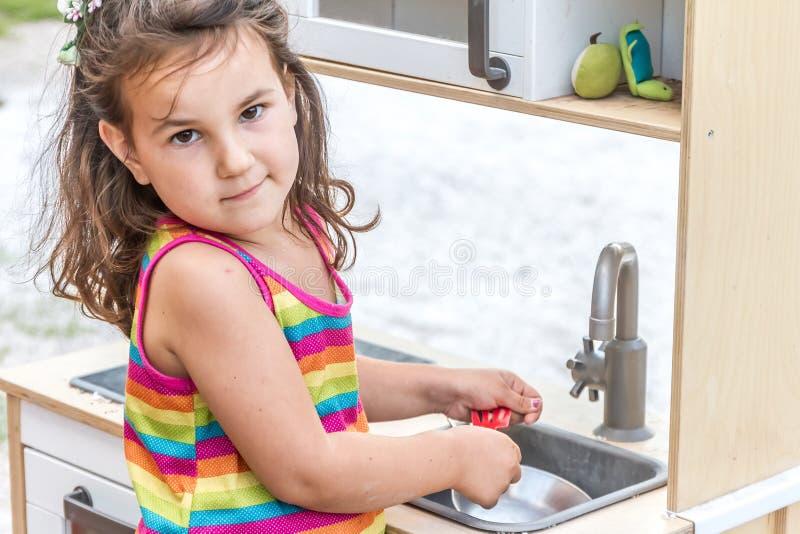 Porträt im Freien des jungen glücklichen lächelnden Mädchens, das Spielzeugküche spielt stockbild