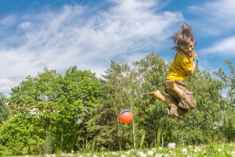 Porträt im Freien des jungen glücklichen spielenden Jungen wird Ball auf natürlichem lizenzfreies stockfoto