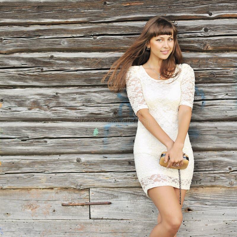 Porträt im Freien des jungen hübschen Mädchens im weißen Kleid mit handba stockbild