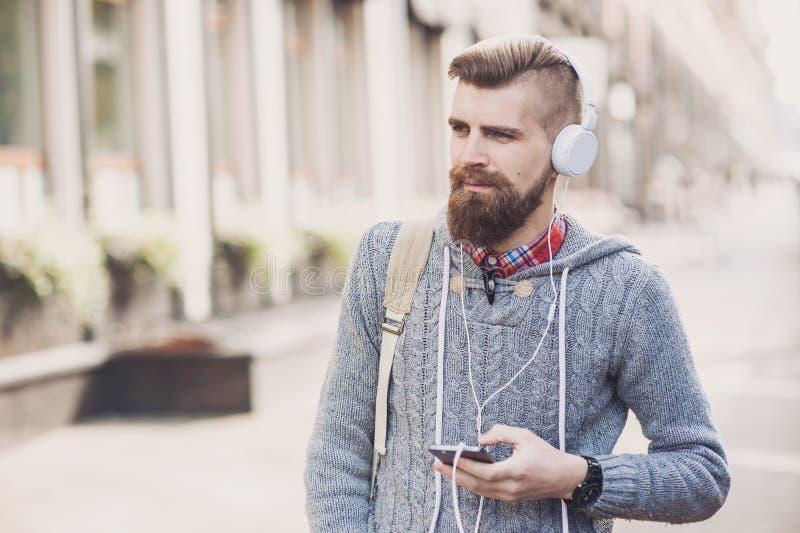 Porträt im Freien des modernen jungen Mannes mit intelligentem Telefon in der Straße stockfotos