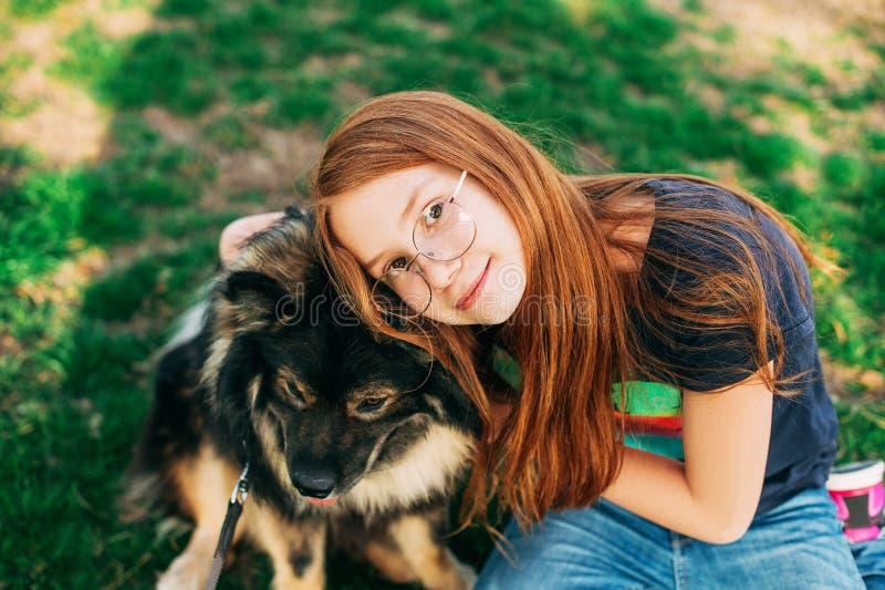 Porträt im Freien des netten rot-angestellten Kindermädchens, das ihren Hund umarmt stockfoto