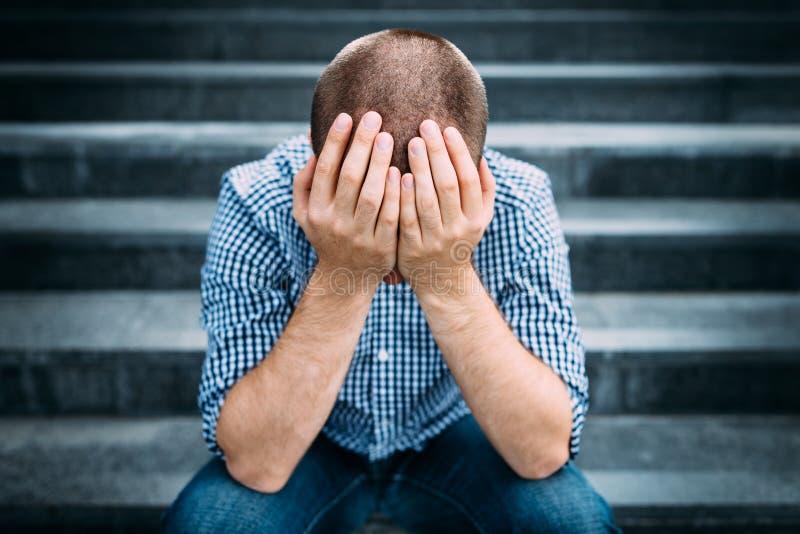 Porträt im Freien des traurigen jungen Mannes, der sein Gesicht mit den Händen bedeckt lizenzfreie stockfotos