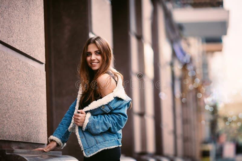 Porträt im Freien einer jungen schönen modernen glücklichen Dame, die auf einer Straßenstadt aufwirft Vorbildliche tragende stilv lizenzfreie stockbilder