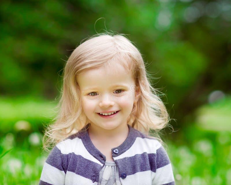 Porträt im Freien eines lächelnden kleinen Mädchens mit dem blonden gelockten Haar stockbild