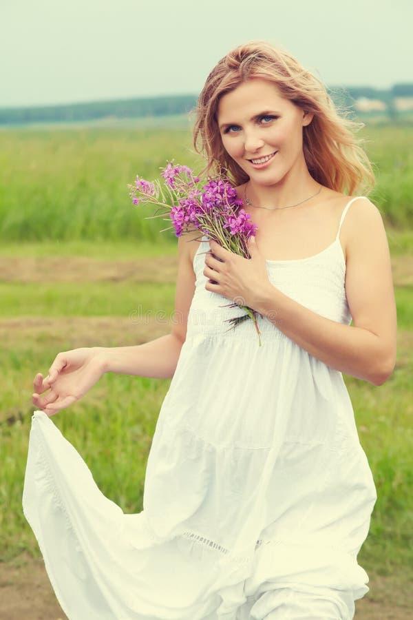 Porträt im Freien mittleren gealterten Blondine attraktives sexy Mädchen auf einem Gebiet mit Blumen lizenzfreie stockfotografie