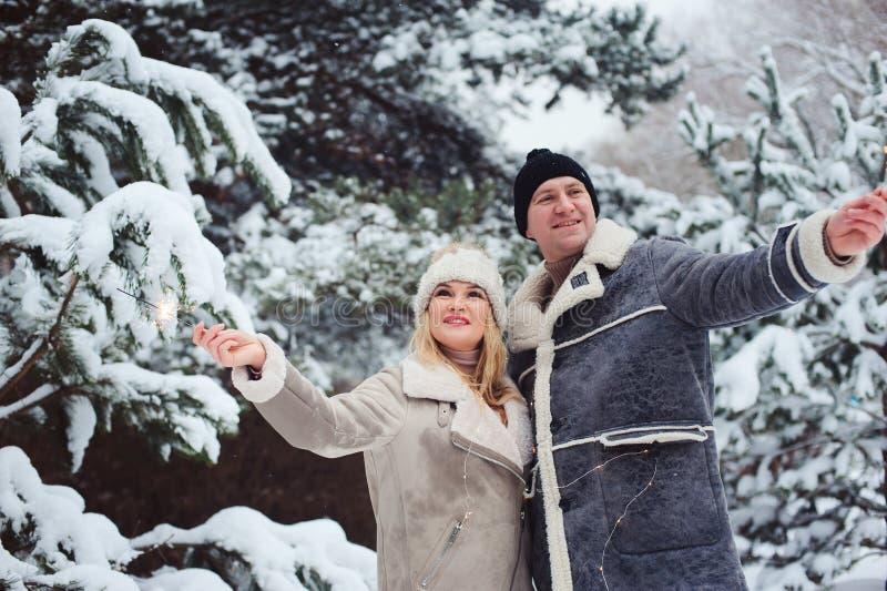 Porträt im Freien von den glücklichen romantischen Paaren, die Weihnachten mit brennenden Feuerwerken im schneebedeckten Wald fei stockbilder