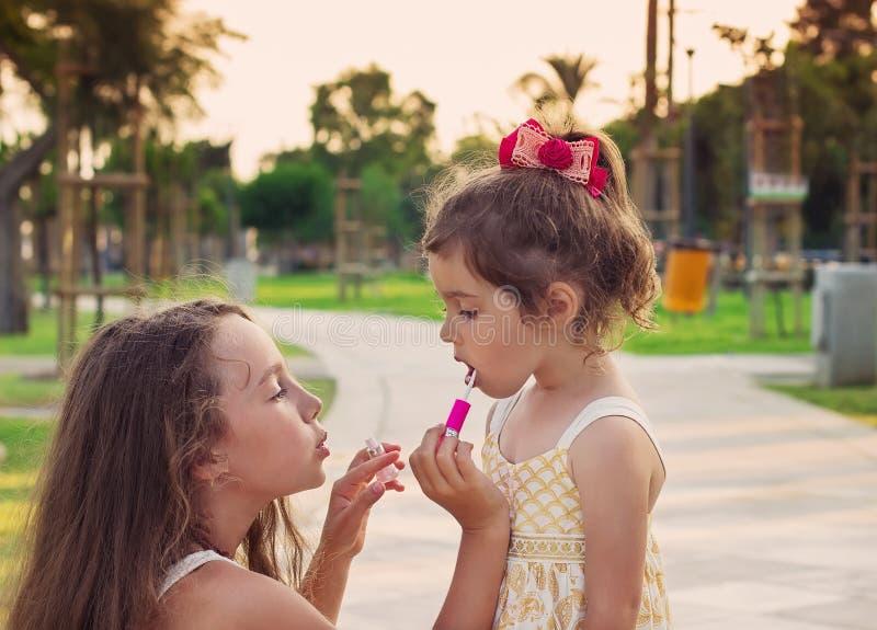 Porträt im Freien von den kleinen schönen Mädchen, die Lippen des Rosas malen stockbild