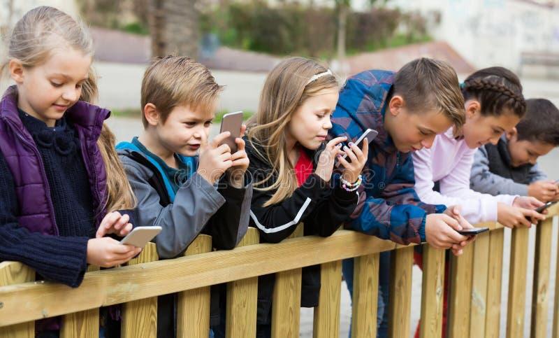 Porträt im Freien von den Mädchen und von Jungen, die mit Telefonen spielen stockbilder