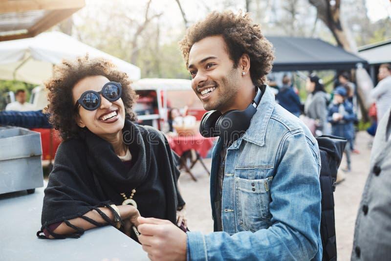 Porträt im Freien von glücklichen Afroamerikanerpaaren mit Afrofrisuren, lehnend auf Tabelle während auf Lebensmittelfestival lizenzfreies stockbild