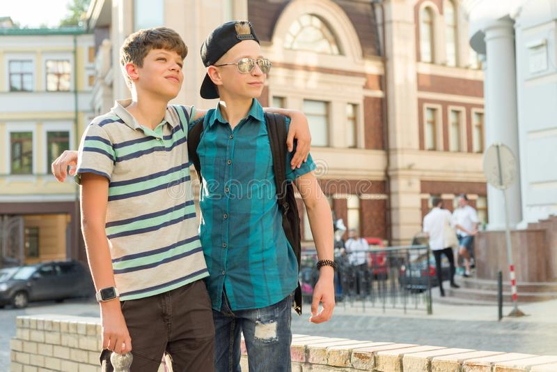 Porträt im Freien von zwei Freundjungenjugendlichen 13, von 14 Jahren alten Unterhaltung und Lachen auf Stadtstraße stockbild