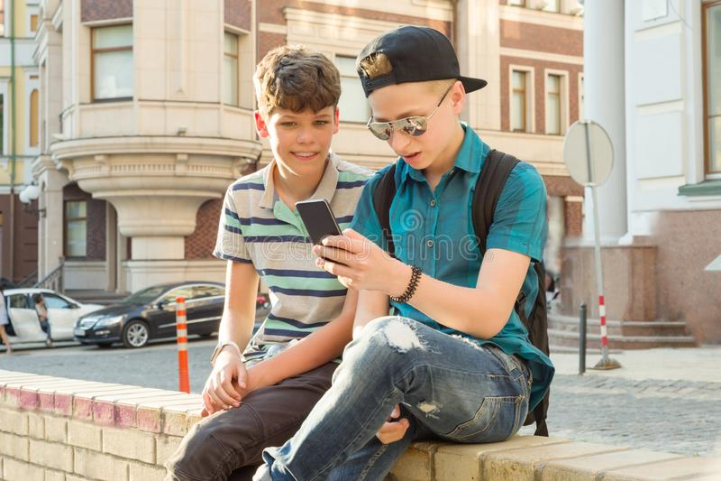 Porträt im Freien von zwei Jungen 13, 14 Jahre alt, sprechend auf Stadtstraße, Freundlachen und betrachten Handy stockbild