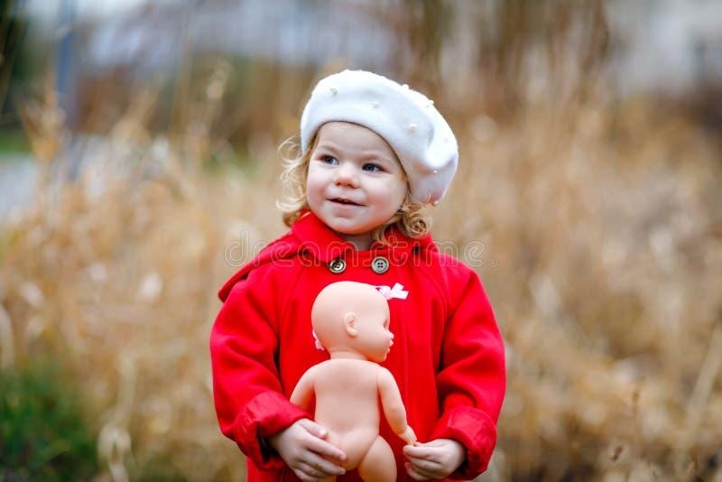 Porträt im Freien wenigen netten Kleinkindmädchens im roten Mantel und im weißen Modehuttrog mit Spielzeugpuppe Gesundes glücklic lizenzfreie stockfotografie