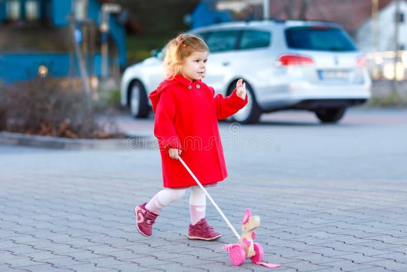 Porträt im Freien wenigen netten Kleinkindmädchens am sonnigen Tag roten Mantel-AON-Frühlinges mit hölzernem Spielzeug des Stoßes lizenzfreies stockbild