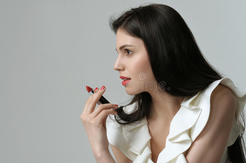 Porträt im Profil eines hübschen Mädchens, das einen Lippenstift L hält stockfoto