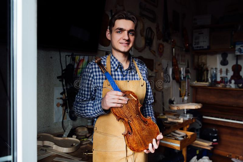 Porträt Junge luthier mit einer handgefertigten Violine in seiner Werkstatt mit den Werkzeugen stockbild