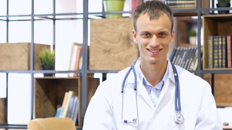 Porträt jungen Doktors lächelnd an der Kamera in einem Büro am Krankenhaus stockbilder