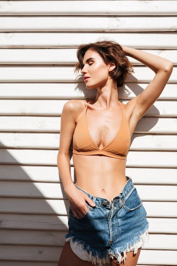 Porträt junger Dame in den Bikini- und Denimkurzen hosen, die mit weißen hölzernen Brettern auf Hintergrund stehen Schönes Mädche stockfotos