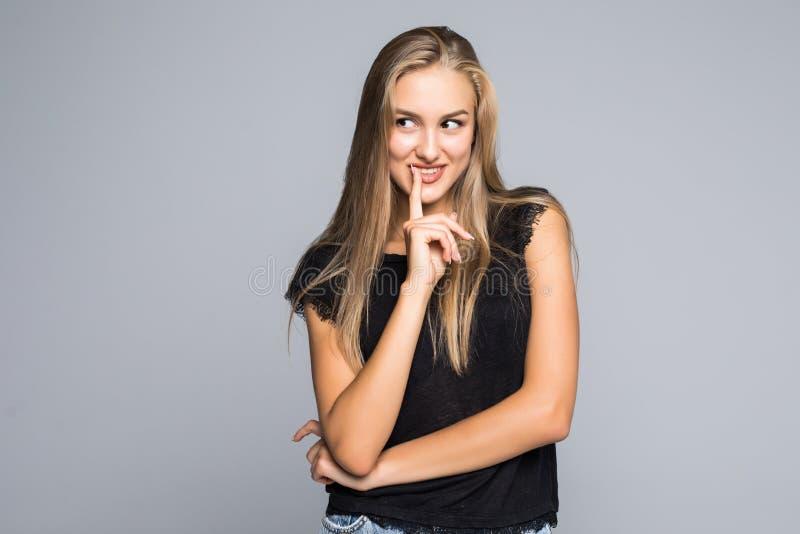 Porträt junger Dame denkende Geste mit dem Finger zur Lippe, geöffneter Mund zeigend, über grauem Hintergrund lizenzfreie stockfotografie