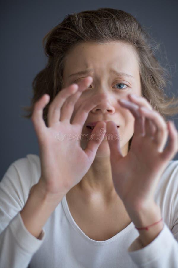 Porträt junger erschrockener Dame, die traurig in camera während Händchenhalten vor ihrem Gesicht schaut stockbilder