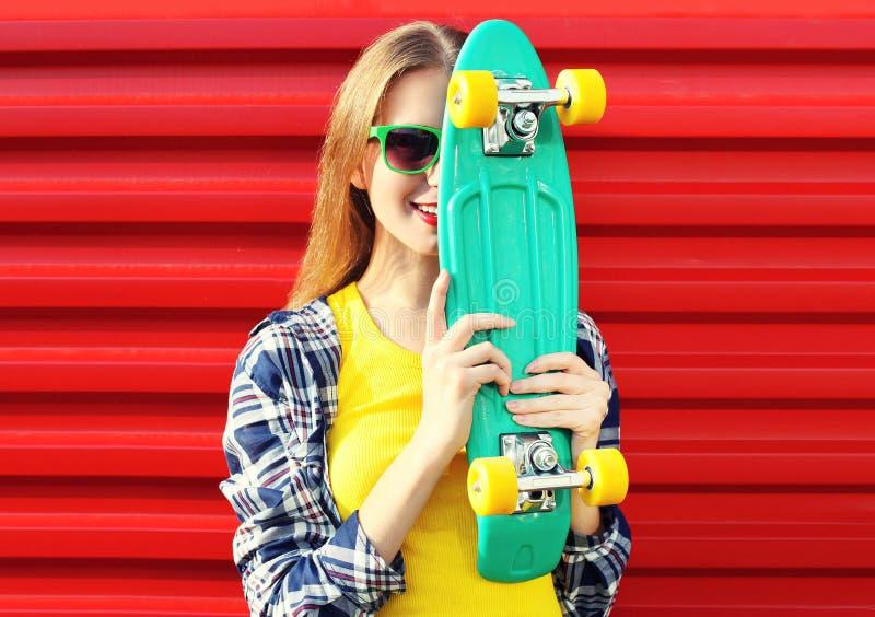 Porträt kühlen Mädchens der Mode des recht mit dem Skateboard, das Spaß hat lizenzfreie stockfotografie