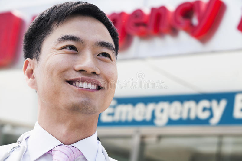 Porträt lächelnden Doktors außerhalb des Krankenhauses, Unfallstation unterzeichnen herein den Hintergrund, Nahaufnahme stockfoto