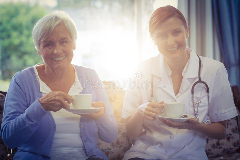 Porträt lächelnden Doktors und des Patienten, die Tee trinken lizenzfreie stockfotografie