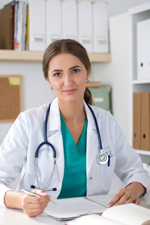 Porträt lächelnden freundlichen Medizindoktors, der an ihrem offi sitzt lizenzfreie stockbilder