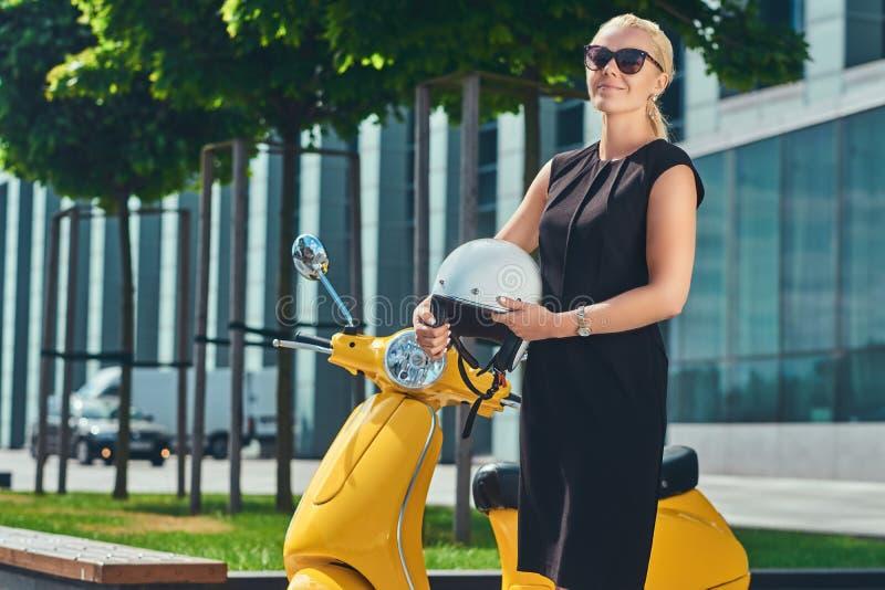Porträt lächelnden reizend schönen Blondine, die ein schwarzes Kleid und Sonnenbrille, Griffe ein motocycle Sturzhelm tragen lizenzfreie stockfotografie