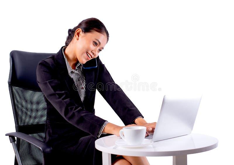 Porträt lokalisierte, die südostasiatische Geschäftsfrau dunkelgrauen Anzug trägt, arbeitet im Büro durch Anruf zu jemand auf wei lizenzfreie stockfotos