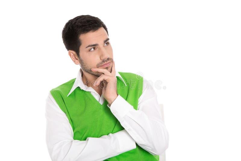 Porträt: Lokalisierter junger Geschäftsmann im Grün, das zweifelhaft schaut lizenzfreies stockbild