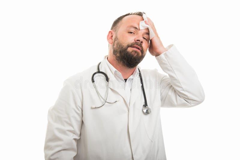 Porträt männlichen Doktors seine Stirn mit Serviette trocknend lizenzfreies stockbild