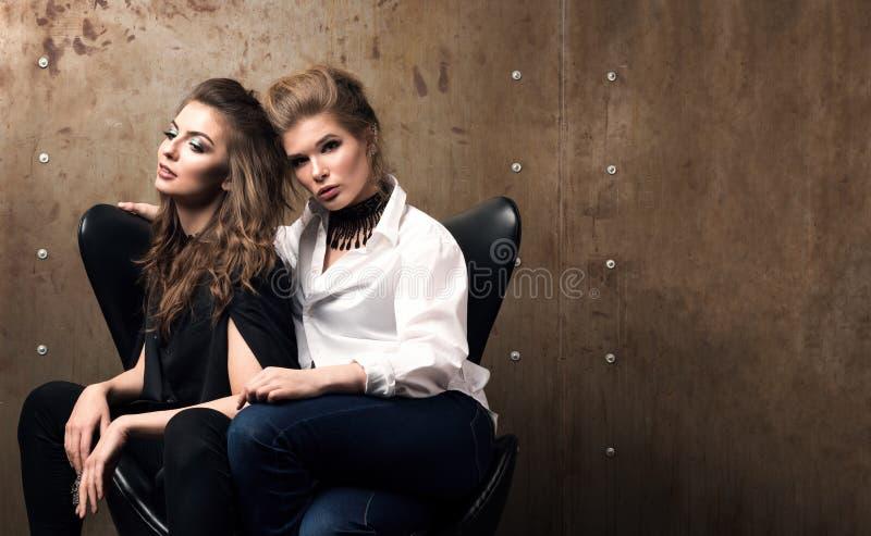 Porträt mit freiem Raum Zwei attraktive junge Frauen, die im resle aufwerfen, welches das Metall ummauern stockfotografie