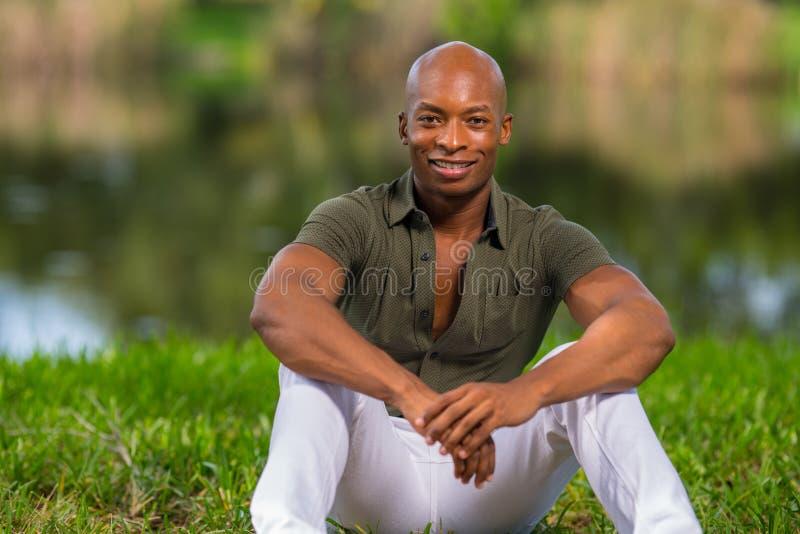 Porträt-moderner Afroamerikanermann, der auf Gras im Park sitzt Mann ist, betrachtend lächelnd und Kamera stockfotografie