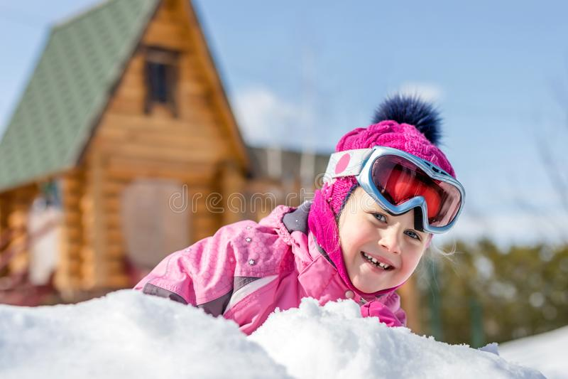 Porträt nettes ittle kaukasischen Mädchens in den Sportwinterjacken- und -skischutzbrillen, die den Spaß draußen spielt mit Schne stockbild