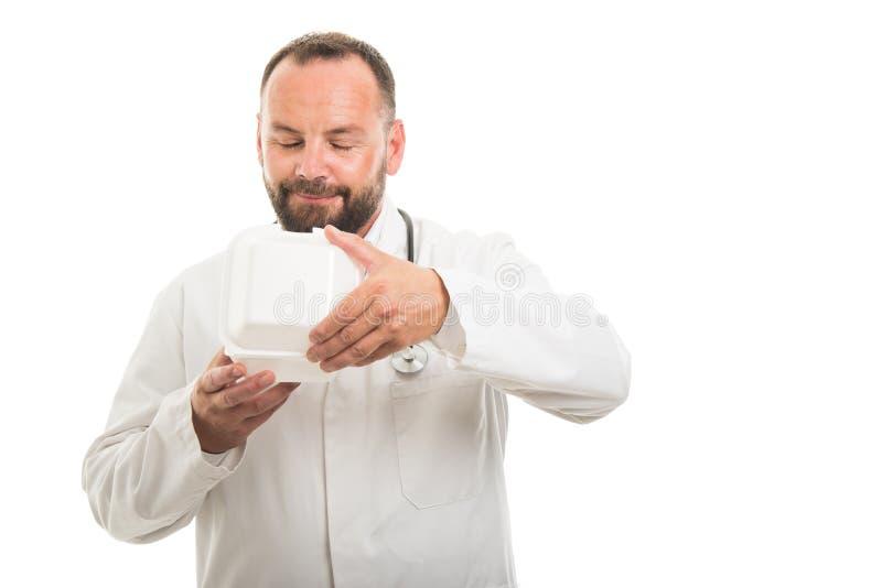 Porträt riechender Brotdose männlichen Doktors stockfoto