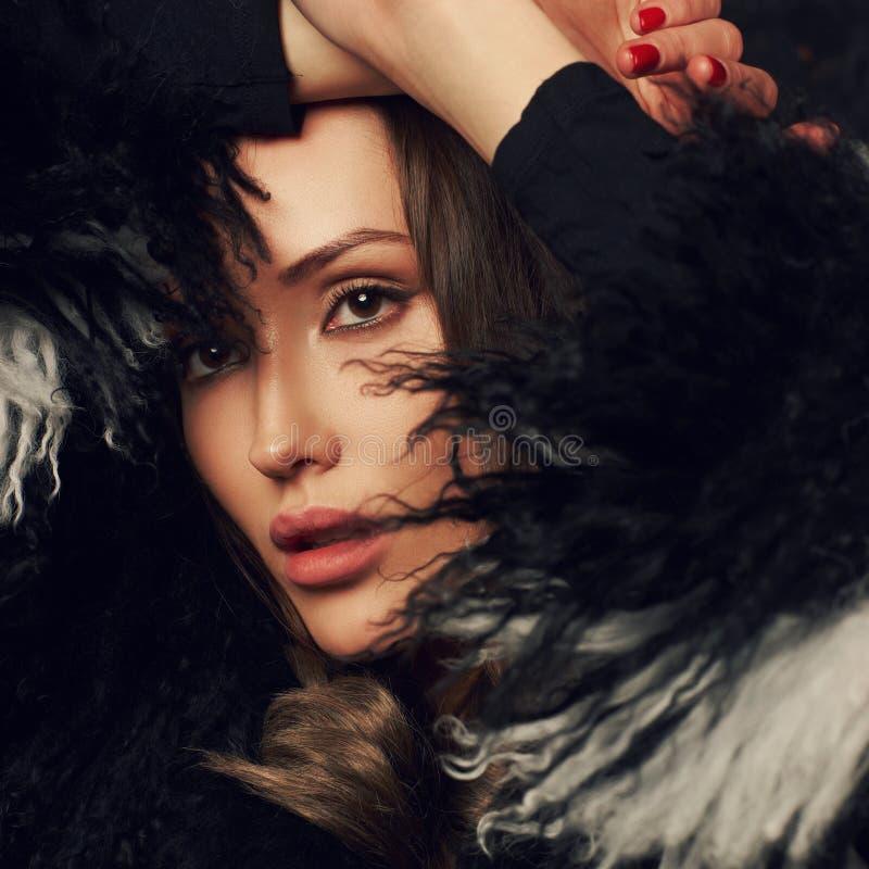 Porträt schöne Brunettefrau des tragenden Faux-Pelzmantels mit stockbilder